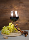 Glass of red wine, grapes and corkscrew made of vine Stock Images