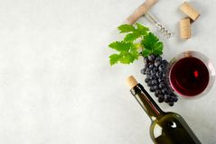 A glass of red wine and grapes. A glass of red wine, grapes and grape leaves wine bottle and corks on the table. Top view with copyspace for your text royalty free stock image