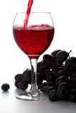 Glass of red wine and grapes isolated Stock Images