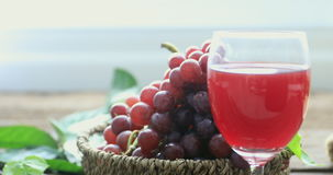 Glass of red wine and grapes on a old wooden background. Selective focus stock footage