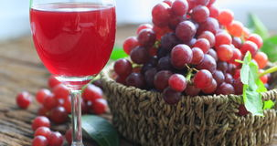 Glass of red wine and grapes on a old wooden background. Selective focus stock video footage