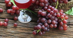 Glass of red wine and grapes on a old wooden background. Selective focus stock video