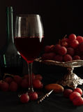 Glass of red wine and grapes Stock Photos