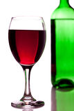 Glass of red wine and green bottle Royalty Free Stock Image