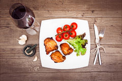 Glass of red wine, grilled meat on the white plate, tomatoes, le. Ttuce, . Top view. Sepia toned. Horizontal Royalty Free Stock Photo