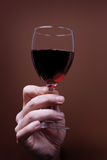 Glass of red wine in hand. On brown background Stock Photo