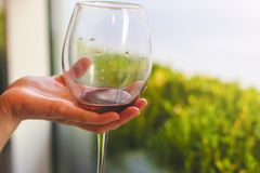 Glass of red wine in the hand stock photography