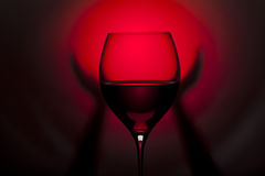 Glass with red wine with hands on red and black background Royalty Free Stock Photos