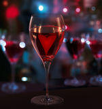 Glass of red wine, with heart. Blurred City Lights Stock Images
