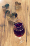 Glass of red wine with hearts Stock Photo