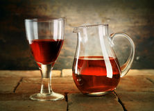A glass of red wine with a jug of wine Royalty Free Stock Image