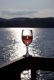 Glass of red wine at lake. A classic-shaped wine glass filled with red wine, sitting on the railing of a deck with the sunlit lake behind it.  The setting sun Stock Image