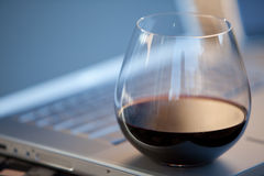 Glass of red wine on laptop. Glass of red wine on a laptop computer outside royalty free stock image