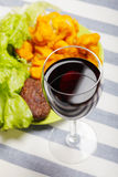 Glass of red wine and meal Stock Photography