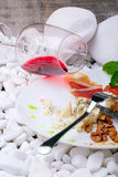 A glass of red wine and meat dish on the white stones. Slices of salty prosciutto and Roquefort cheese on a white plate. Royalty Free Stock Images