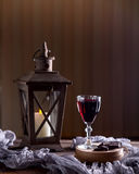 Glass with red wine. Near broken chocolate. Lantern with a candl Royalty Free Stock Photo