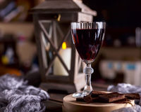 Glass with red wine. Near broken chocolate. Lantern with a candl Royalty Free Stock Images