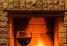 Glass of red wine near cozy fireplace, in country house, winter vacation, horizontal. Tranquil scene before cozy fireplace, with glass of red wine , in country royalty free stock image