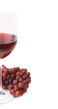 Glass of red wine next to a branch of grapes Royalty Free Stock Photos