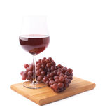 Glass of red wine next to a branch of grapes Stock Photos