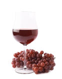 Glass of red wine next to a branch of grapes Royalty Free Stock Photo