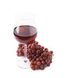 Glass of red wine next to a branch of grapes Stock Image