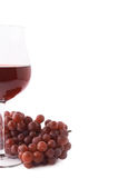 Glass of red wine next to a branch of grapes Stock Photo