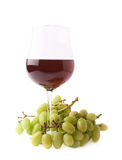 Glass of red wine next to a branch of grapes Royalty Free Stock Image