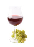 Glass of red wine next to a branch of grapes Stock Images