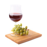 Glass of red wine next to a branch of grapes Royalty Free Stock Photography