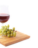 Glass of red wine next to a branch of grapes Stock Photography
