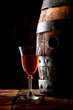 A glass of red wine next to an oak cask. A glass of red wine next to an old oak cask with its stopper out Royalty Free Stock Image