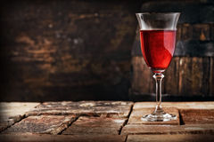 A glass of red wine on an old rustic table Royalty Free Stock Photography