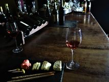 Glass of red wine,  olives, prosciutto, salami, aged cheese on a table at a cozy bar royalty free stock images
