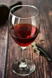 Glass of red wine over rustic, wooden textured table. Dark photo. Glass of red wine over rustic, wooden textured table, background, party, food, vintage, summer royalty free stock images