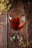Glass of red wine over rustic, wooden textured table. Dark photo. Glass of red wine over rustic, wooden textured table, background, party, food, vintage, summer stock photography