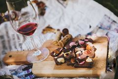 Glass with red wine and pieces of chocolate with nuts and raisins. Stands on cutting board on background of newspapers on the ground outdoors. Alcoholic drink Royalty Free Stock Images
