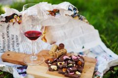 Glass with red wine and pieces of chocolate with nuts and raisins. Stands on cutting board on background of newspapers on the ground outdoors. Alcoholic drink Stock Photos