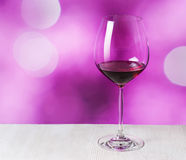 Glass of red wine on purple background Royalty Free Stock Images
