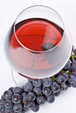Glass of Red Wine and Purple Grapes. An elegant glass of red wine and a bunch of purple grapes stock photos