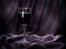 Glass of red wine on purple rippled silk fabric. Royalty Free Stock Image
