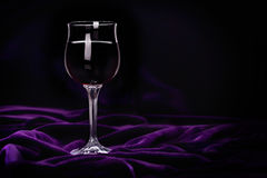 Glass of red wine on purple rippled velvet fabric. Romantic dinner concept Royalty Free Stock Image