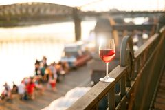 Glass of red wine on a railing with sunset in a Prague city. Concept of free time in the city and drinking alcohol. Glass of red wine on a railing with sunset royalty free stock photo