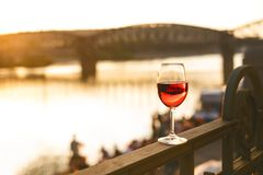 Glass of red wine on a railing with sunset in a Prague city. Concept of free time in the city and drinking alcohol. Glass of red wine on a railing with sunset Stock Photo