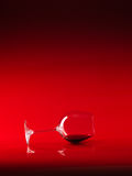 Glass of red wine on red background Royalty Free Stock Images