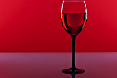 Glass of red wine on a red background Royalty Free Stock Image