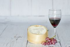 Glass of red wine, red grapes and camembert cheese in wooden box - horizontal Stock Photos