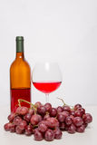 Glass of red wine and red grapes Stock Images