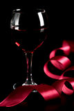Glass of red wine and red ribbon. Over black background Stock Image