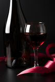 Glass of red wine and red ribbon over black Stock Image